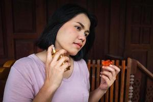 kvinna som sprayar parfym på hennes hals. foto