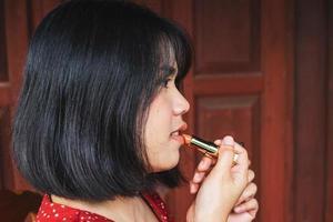 kvinna applicera läppstift foto
