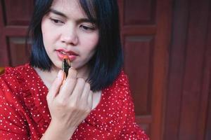 närbild av en kvinna som applicerar läppstift foto