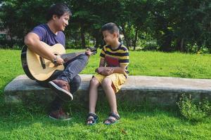 far som spelar gitarr för sin son foto