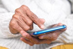 äldre kvinnas hand genom att använda smart telefon på nära håll