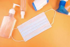 kirurgiska masker, termometer och handdesinfektionsmedel på orange bakgrund