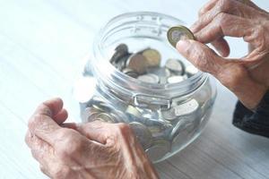närbild av äldre kvinnas hand som sparar mynt i en burk foto