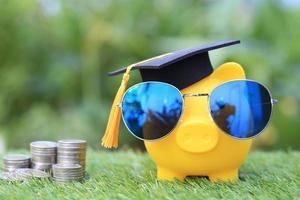 examenhatt på en gyllene spargris med solglasögon och en stapel mynt på en naturlig grön bakgrund, vilket sparar pengar för utbildningskoncept foto