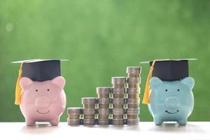 examenhattar på spargrisar och en stapel mynt på en naturlig grön bakgrund, vilket sparar pengar för utbildningskoncept foto