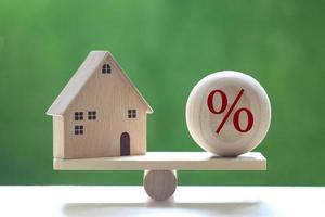 modellhus med en procentuell symbolikon i träskala på en naturlig grön bakgrund, räntesats upp och bankkoncept foto