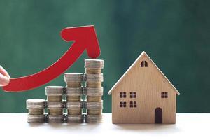 en kvinnas hand som håller en röd pil på en stapel myntpengar med ett modellhus på en naturlig grön bakgrund, affärsinvesteringar och fastighetskoncept