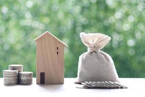 modellhus med en stapel mynt på en naturlig grön bakgrund, vilket sparar pengar för att förbereda sig för framtiden och investeringskonceptet foto