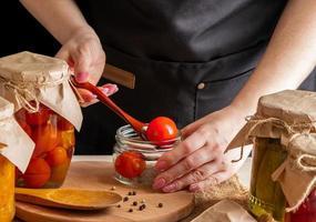 en kvinna jäser grönsaker. inlagda tomater i burkar. bevara höstskörden. organisk mat. foto