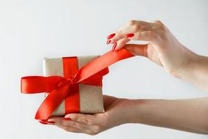 gåva med ett rött band i händerna på en vit bakgrund foto