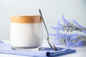 dalgona kaffe. glas trendig mjölkdryck på en blå servett.