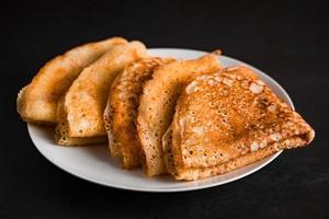 tunna pannkakor på en tallrik på en svart bakgrund, traditionell rysk mat. foto