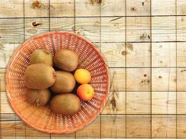 kiwi och aprikoser i en korg på en träbord bakgrund foto
