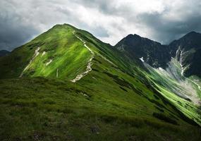 gröna berg och stormig himmel foto