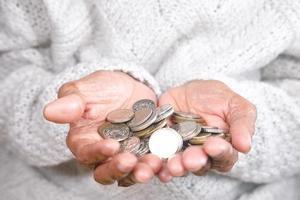 kvinna som håller många mynt foto