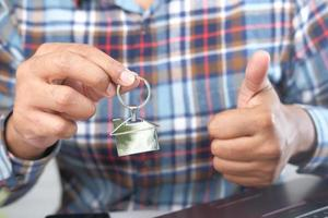 man håller nyckelring med ett hem
