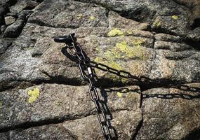 rostig järnkedja på en granitsten foto