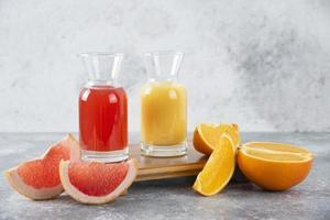 två glas grapefrukt och apelsinjuice på en stenbakgrund