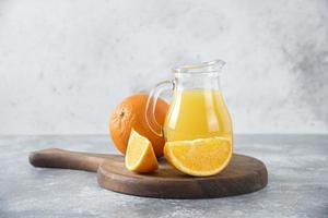 en glaskanna med färsk juice med hel och skivad apelsinfrukt placerad på en träskiva