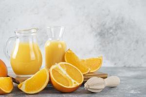 glasskannor med färsk juice med skivad apelsinfrukt och en träreamer