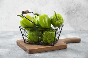 färska gröna paprika i en metallisk korg placerad på en stenbakgrund