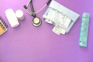 blisterförpackning, termometer och stetoskop på lila bakgrund foto