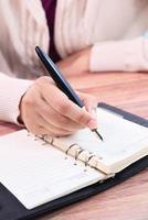 närbild av kvinnan skriver i anteckningar