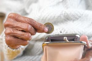 gammal kvinna att sätta mynt i myntväskan foto