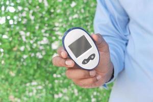 ung man som håller diabetiska mätverktyg