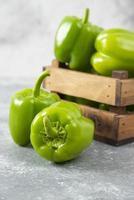 färska gröna paprika placerade i en gammal träask