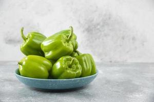 färska gröna paprika placerade på en blå tallrik på ett stenbord