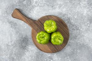 färska gröna paprika placerade på ett trä runt bräde