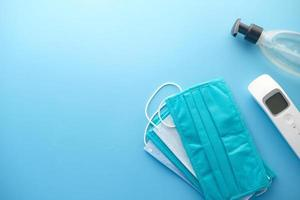 kirurgiska masker, termometer och handdesinfektionsmedel på blå bakgrund