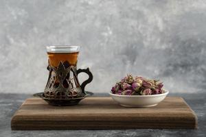 en glass kopp varmt te med torkade rosor på en träskärbräda foto