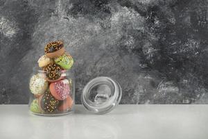 en glasburk full av små färgglada munkar foto