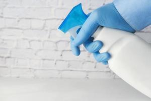 sprutar desinfektionsmedel med handskar på