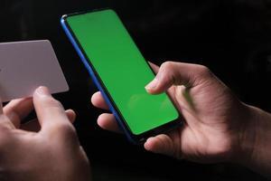 manhand som håller kreditkort och använder smarttelefonshopping online foto