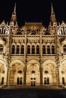 det ungerska parlamentet i Budapest på Donau i nattlamporna på gatlyktorna