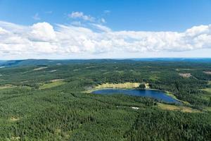 Flygfoto över ett skogsmark i sverige med en sjö i form av ett fotavtryck