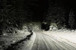 hal vinterväg upplyst av helljusstrålkastare på natten