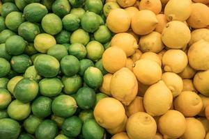 räknare av staplade färska citroner och limefrukter