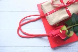 ovanifrån av en presentförpackning, väska och rosor på bordet foto