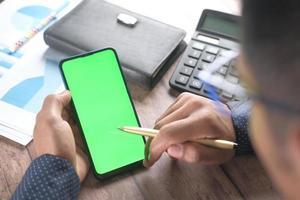 bakifrån av mans hand med smart telefon vid skrivbordet