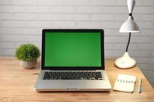 bärbar dator med grön skärm vid skrivbordet