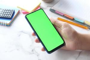 grön skärm smart telefon på neutral skrivbordsbakgrund