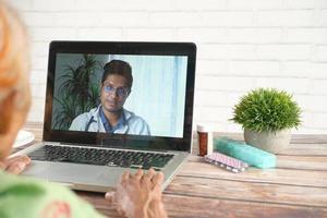 äldre kvinna som har en online-konsultation med läkare foto
