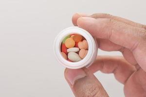 person som håller den vita pillerflaskan