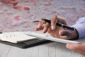 mans hand som arbetar på digital tablet vid kontorsskrivbordet foto