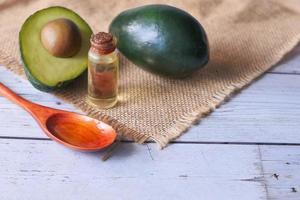 halverad avokado och liten flaska olja på neutral bakgrund