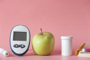 diabetiska mätverktyg och ett äpple på rosa bakgrund